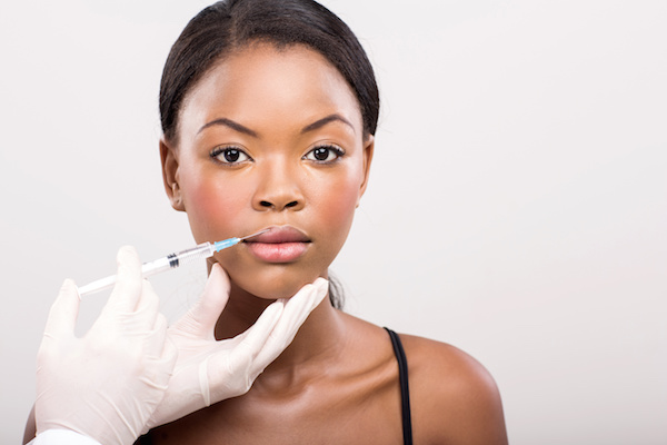 african girl receiving cosmetic injection on her lips